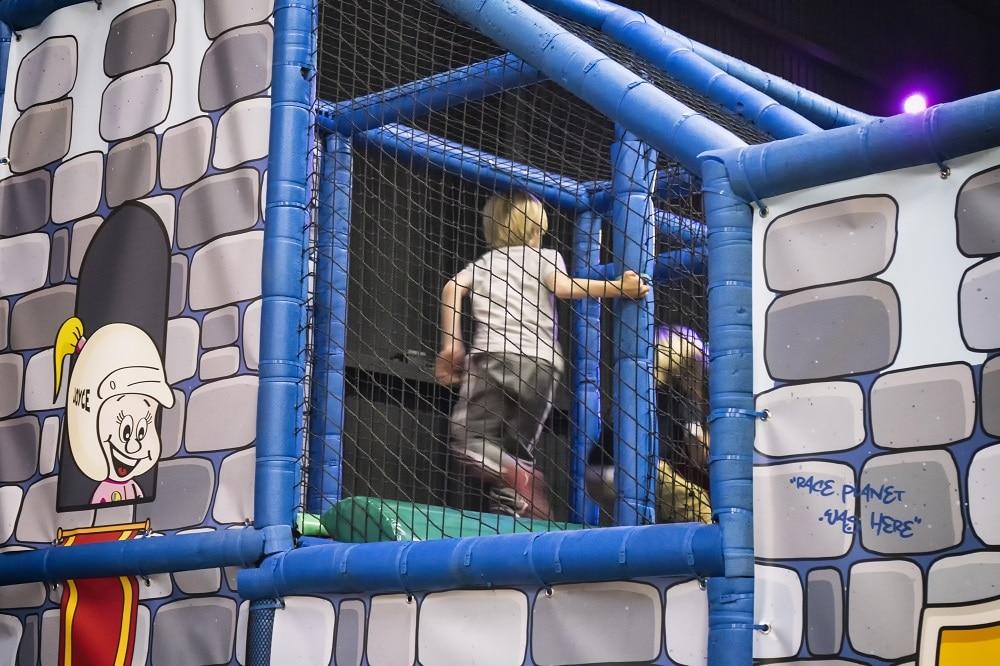 Jongen gaat de hoek om en speelt in het Klimkasteel van het speelparadijs in Amsterdam