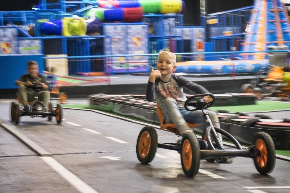 jongen steekt duim omhoog op de skelter tijdens het skelteren op de skelterbaan in het speelparadijs