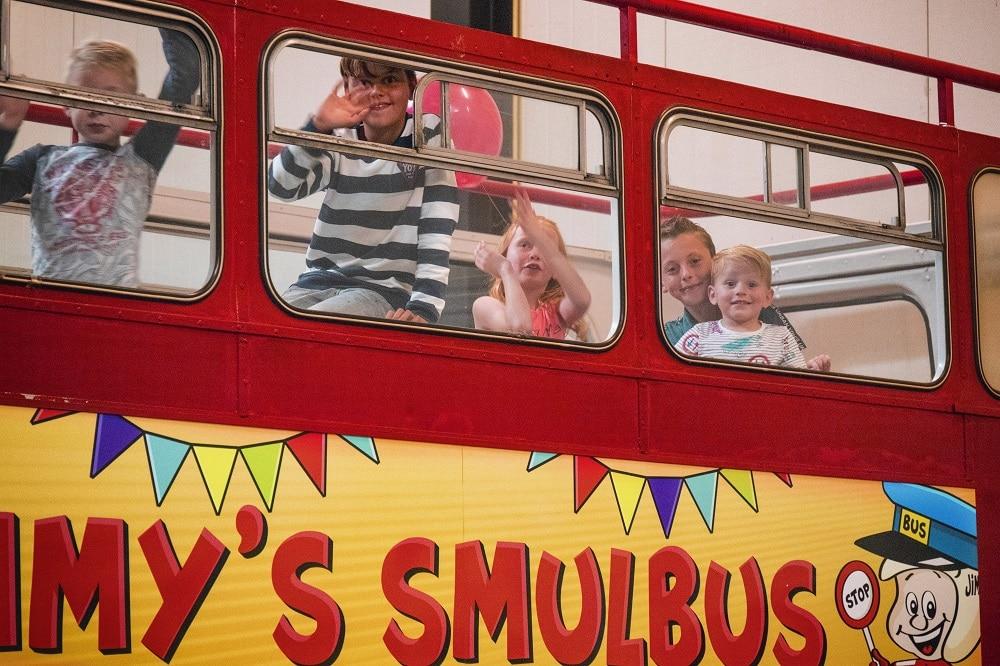 Lachende kinderen bovenin de smulbus om te gaan eten tijdens een kinderfeestje