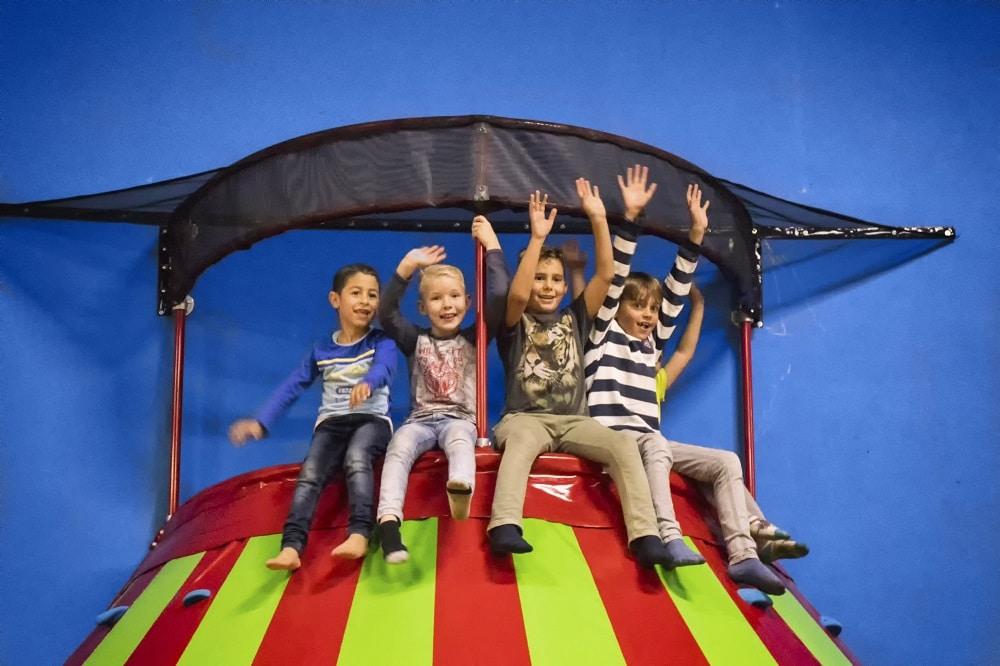 Kinderen zittend bovenop de klautertoren die plezier hebben.