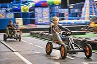 Jongen steekt duim op tijdens het skelter rijden bij Jimmy's Speelparadijs in Amsterdam
