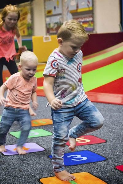 Kinderen hinkelen naast de klautertoren in Jimmy's speelparadijs