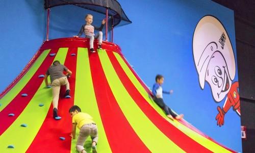 Klautertoren van Jimmy's Speelparadijs met spelende kinderen die omhoog klimmen en naar beneden glijden.