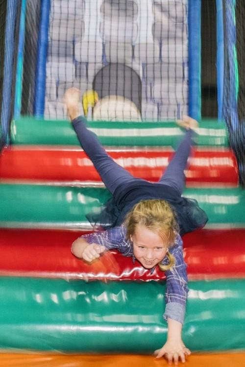 Kind glijdt van een helling in het klimkasteel van Jimmy's Speelparadijs