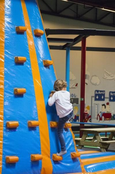 Jongen klimt op de wand van het springkussen naar boven