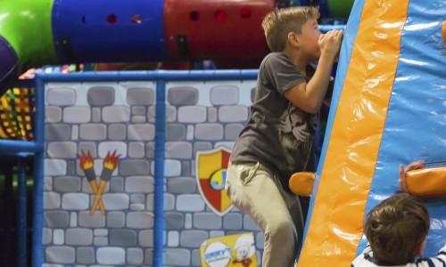 Jongen klimt op de klimwand van het springkussen bij Jimmy's Speelparadijs.
